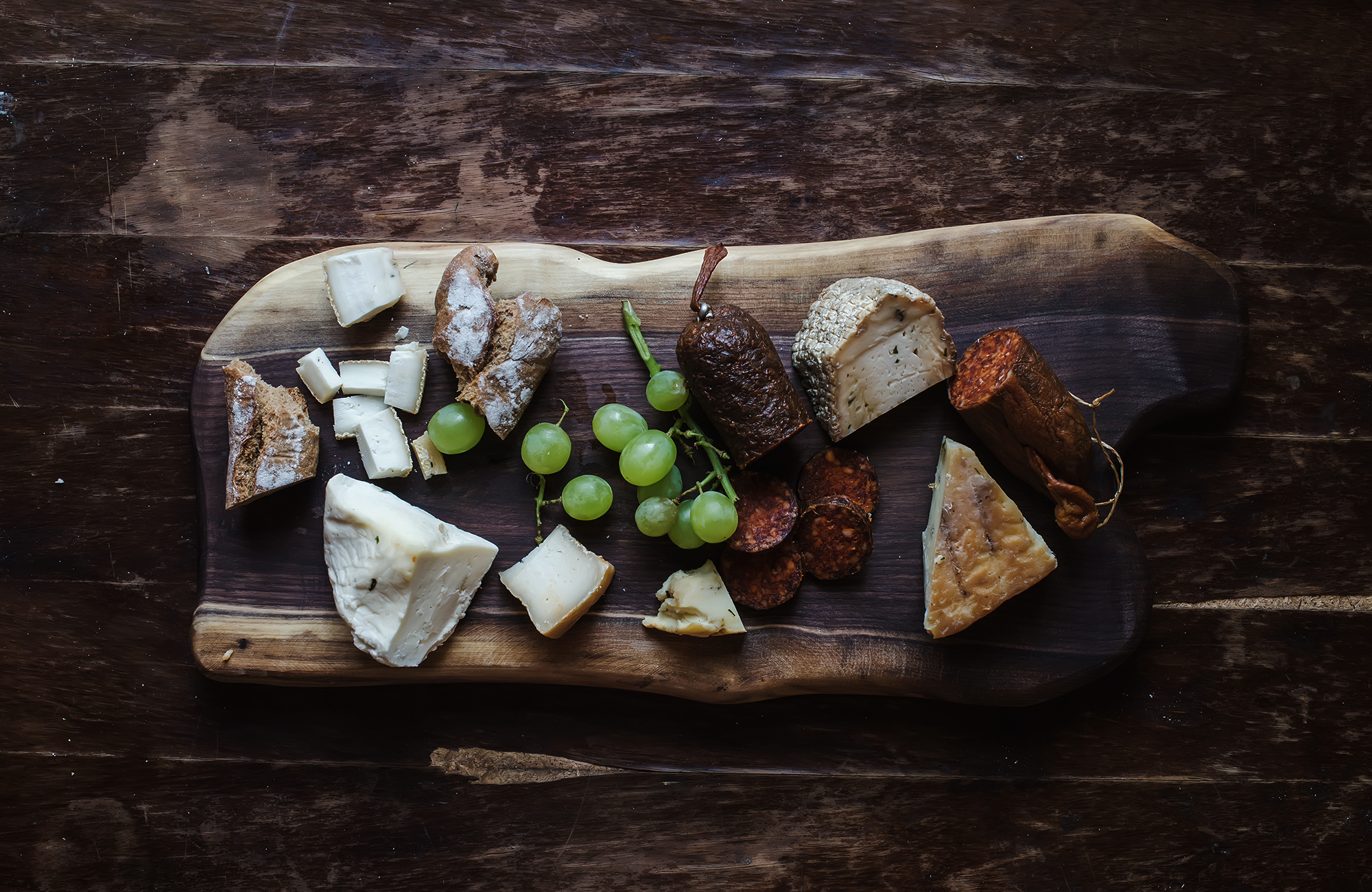 Wine appetizers set: meat and cheese selection, grapes, bread on rustic wooden board over dark wood background.